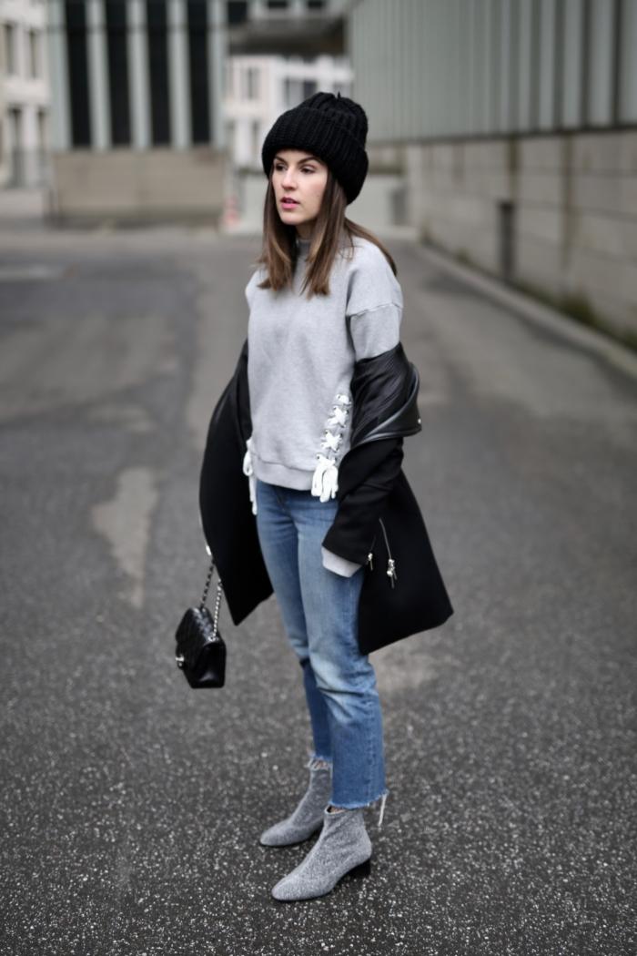 grey sweater, black coat, jeans, grey boots, beanie