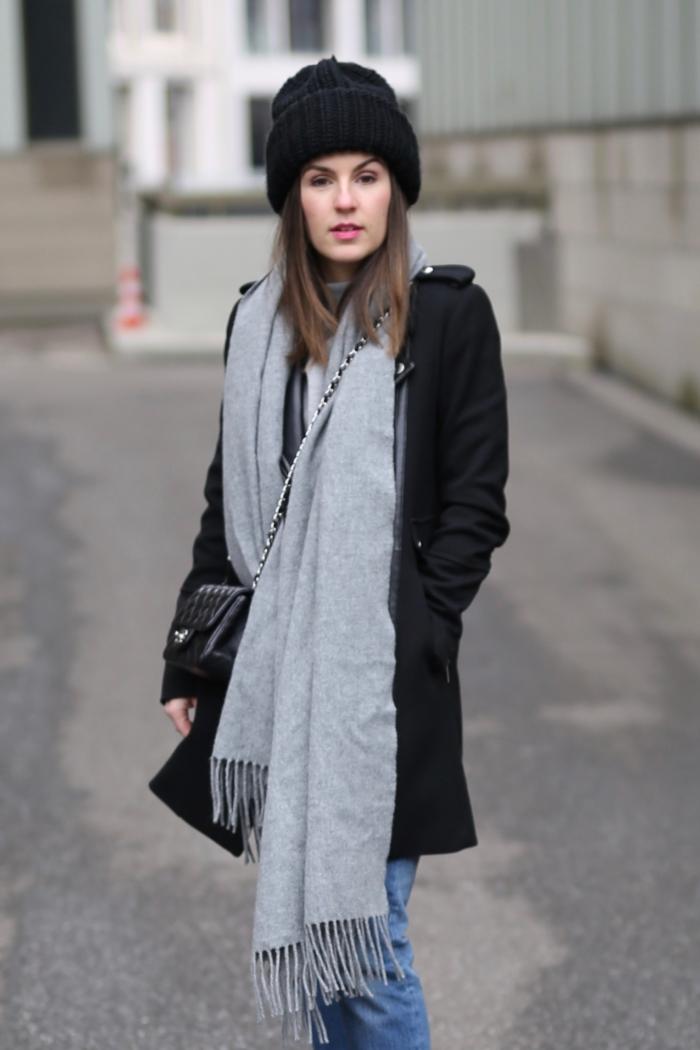 schwarze Beanie, grauer Schal, schwarzer Mantel, Jeans