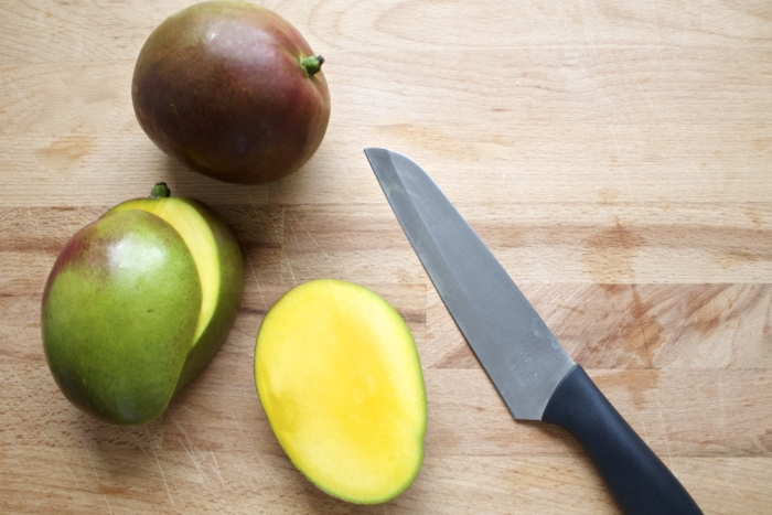 mangos, sliced in half, knife
